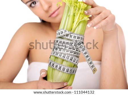 A  woman measuring a vegetable with a measure tape, isolated on white - stock photo