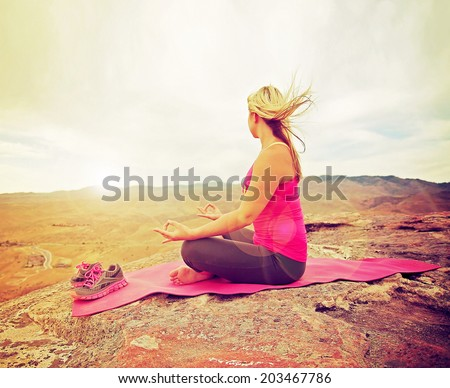 a woman meditating in a yoga pose on a hill top rock done with a soft instagram like glowing filter - stock photo
