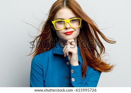 A woman model with a beautiful look looks at the camera, flying hair, a woman wearing glasses