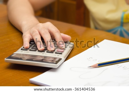 A woman notes and calculates number on the note card with calculator in background