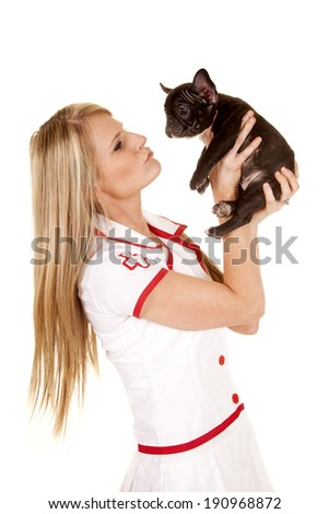 a woman nurse looking up at a little dog, that she is holding in her hand.
