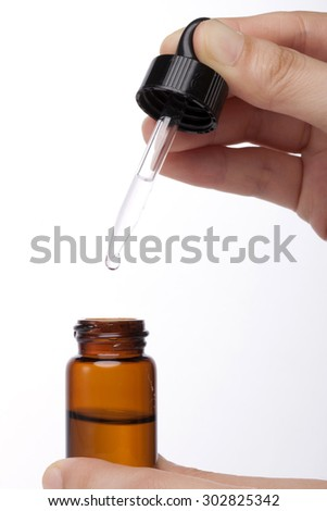 A woman(nurse, scientist) hands hold a spuit(dropping pipet, pipette, medicine dropper) dropping to brown glass container with liquid(fluid) for chemical at the laboratory isolated white.