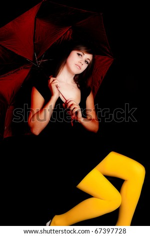 A woman on a black background holding a red umbrella and wearing yellow tights with a serious expression on her face.