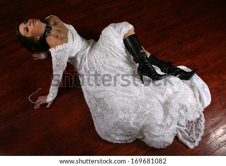 a woman on a stained floor in a wedding dress - stock photo