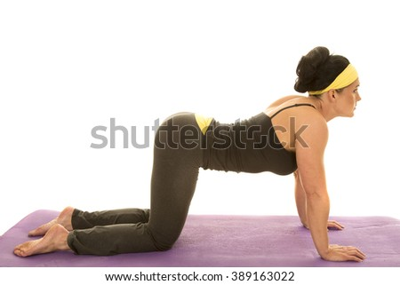 a woman on her hands and knees, stretching out her shoulders and back doing yoga. - stock photo