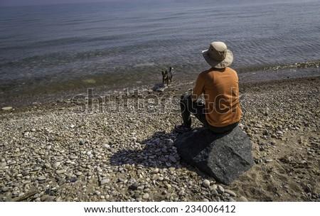 A woman on the beach watching Lake Michigan - stock photo