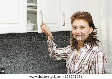 A woman opens a cupboard in the kitchen. - stock photo