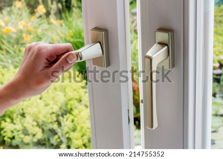 a woman opens a window to ventilate the apartment. fresh air in the room - stock photo