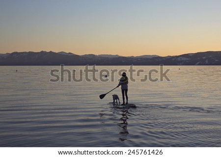A woman paddles on a SUP board with a dog on a lake - stock photo