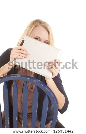 a woman peeking over the top of her electronic tablet while sitting in a chair. - stock photo