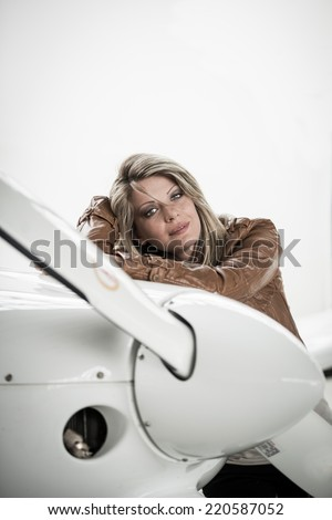 A woman pilot standing next to airplane, looking at camera - stock photo