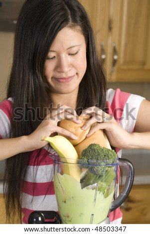A woman placing bread down in a blender of her fruits and vegetables for a healthy smoothie. - stock photo