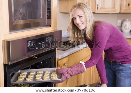 A woman placing the cut out cookies in the oven to bake.