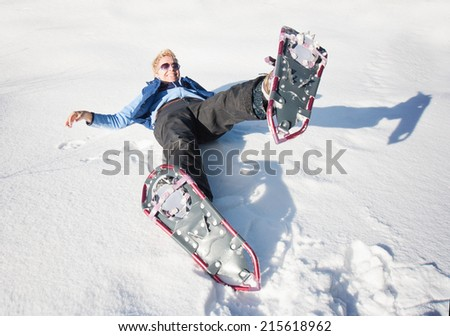 a woman playing in the snow with snow shoes on  - stock photo