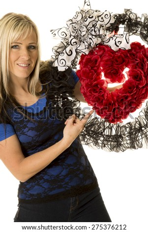 a woman pointing to her heart wreath with a smile. - stock photo