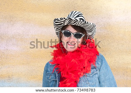 A woman poses against a yellow wall while wearing vintage tiger striped sunglasses and hat.