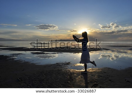 A woman posing with the sun over her head during a sunset - stock photo