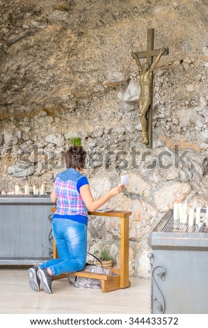 A woman praying with spread arms kneeling in front of the cross in a cave or grotto, outdoors - stock photo