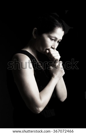 A woman prays on a black background