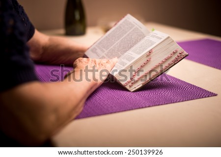 A woman prays to God. In the background holy bible and rosary - stock photo