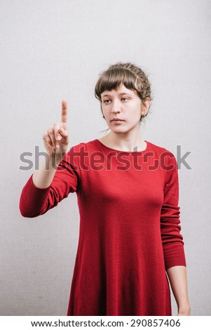 A woman presses a finger. On a gray background. - stock photo