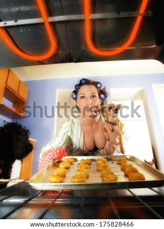 a woman pulling a pan out of the oven - stock photo