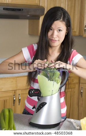 A woman pushing broccoli into her blender trying to make a healthy smoothie. - stock photo