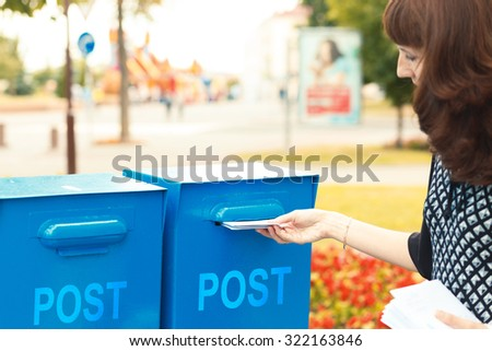 A woman puts letters in the mailbox to send - stock photo