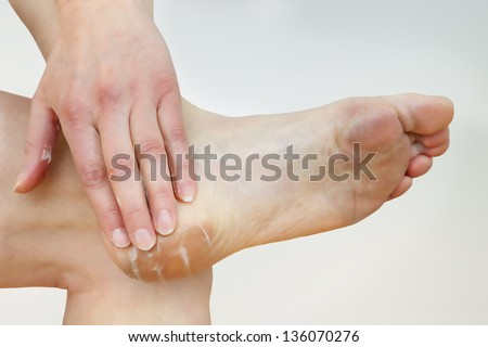 A woman putting cream on her foot - stock photo