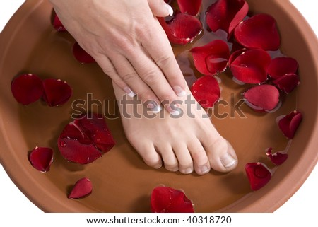 A woman putting her hand and foot  in to a foot bath with roses.