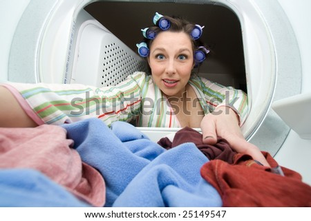 a woman reaching in the dryer for clothes - domestic series - stock photo