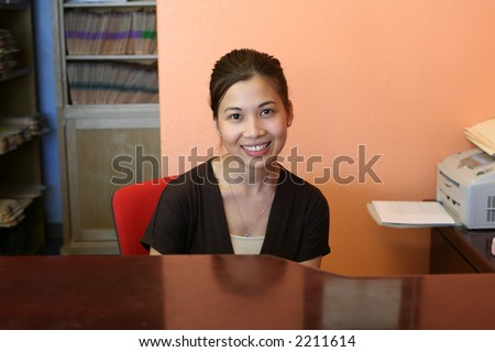 A woman receptionist greeting the customers with a smile - stock photo
