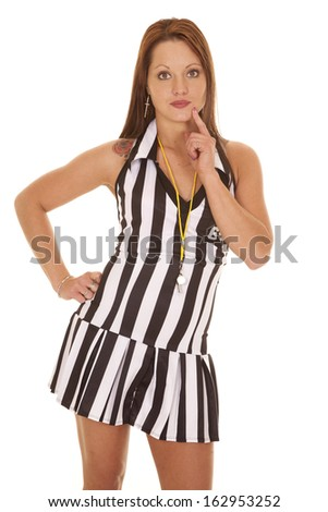 A woman referee is standing with her hand on her hip thinking. - stock photo