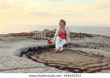 A woman relaxes by the ocean enjoying her morning coffee