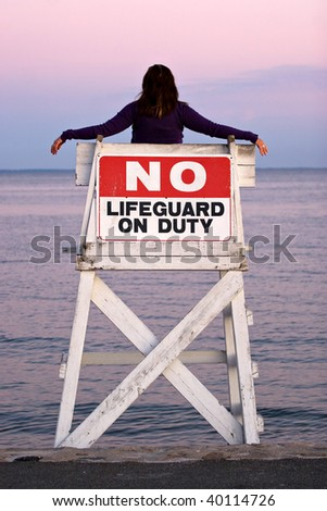 A woman relaxes in a vacant lifeguard chair and watches the beautiful sunset. - stock photo