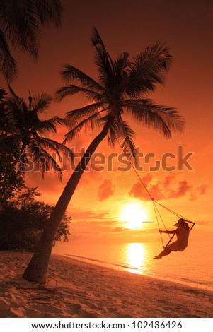 A woman relaxing on a teeter with sunset in a background in Maldives island