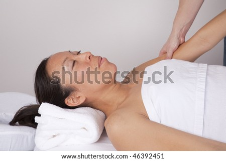 A woman relaxing with her eyes closed while she is getting her arm massaged at the spa.