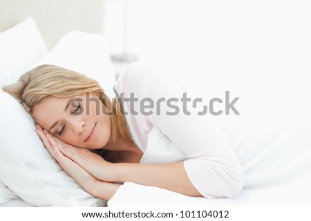 A woman resting in bed with hands beside her head on the pillow.