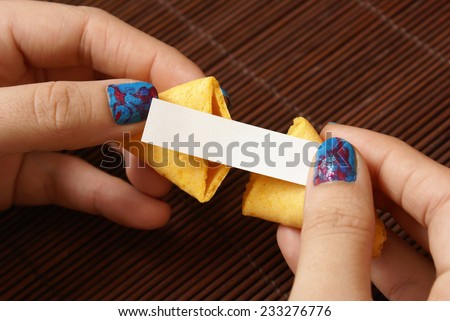 A woman reveals her hidden message within the fortune cookie which is left blank for your own personal text to be inserted. - stock photo