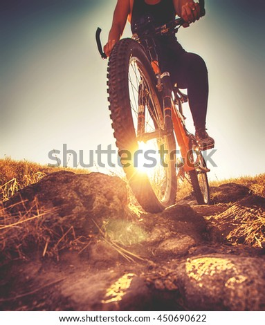 a woman riding a bicycle down a dirt trail with big rocks in the back country to get away from the city toned with a retro vintage instagram filter app or action effect  - stock photo