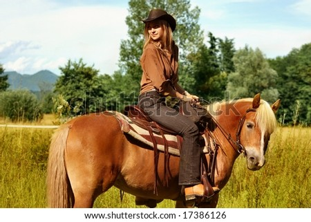 a woman riding horse in countryside - stock photo
