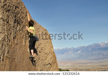 a woman rock climber makes a big reach for the top