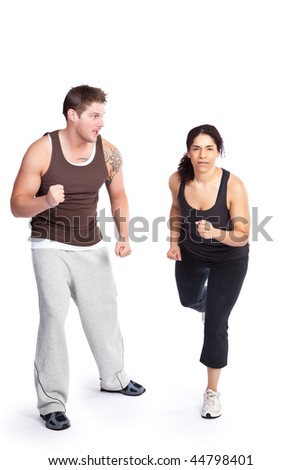 A woman running with her personal trainer - stock photo