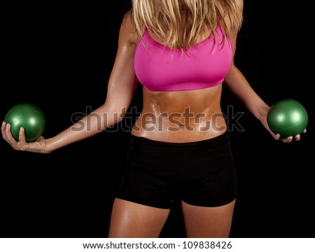 A woman's body holding on to her green exercise balls with sweat dripping off of her body. - stock photo