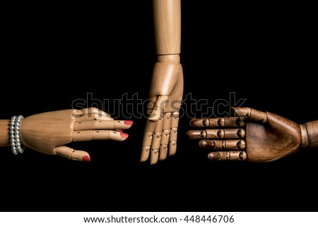 A woman's hand and one hand of black man meet. A white hand opposes. On black background. With copy space. - stock photo