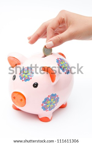 A woman's hand dropping an euro coin into a piggy bank isolated on white. - stock photo