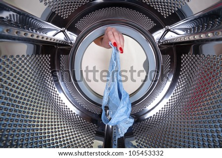 A woman's hand gets blue cowards out of a drum washing machine - stock photo