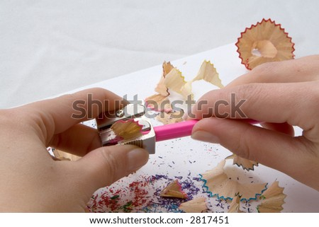 A woman's hand while sharpening a pink colored crayon - stock photo