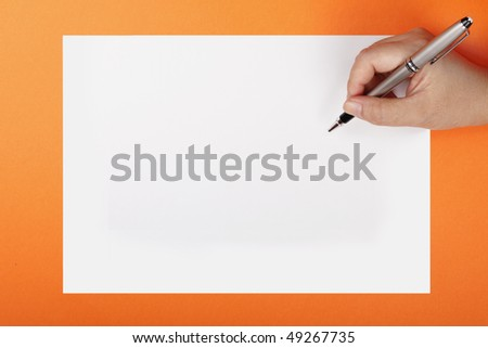 A woman's hand with a pen on a piece of paper - stock photo