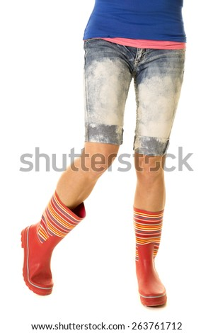 A woman's legs in shorts and her galoshes, ready for the rain. - stock photo